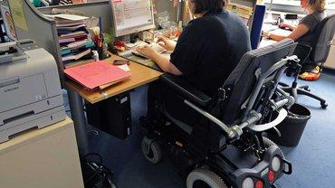 Rollstuhlfahrerin am Schreibtischarbeitsplatz